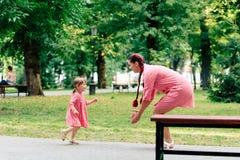 Jeune famille heureuse avec le petit beau bébé avec des yeux bleus marchant en parc d'été au coucher du soleil maman et petit des Photos stock