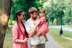 Jeune famille heureuse avec le petit beau bébé avec des yeux bleus marchant en parc d'été au coucher du soleil maman et petit des Photo libre de droits
