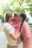 Jeune famille heureuse avec le petit beau bébé avec des yeux bleus marchant en parc d'été au coucher du soleil maman et petit des Photo stock
