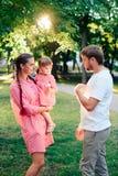 Jeune famille heureuse avec le petit beau bébé avec des yeux bleus marchant en parc d'été au coucher du soleil maman et petit des Photographie stock
