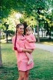 Jeune famille heureuse avec le petit beau bébé avec des yeux bleus marchant en parc d'été au coucher du soleil maman et petit des Photographie stock libre de droits