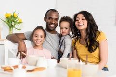 jeune famille heureuse ayant le petit déjeuner ensemble et le regard images stock