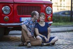 Jeune famille heureuse Couples dans l'amour se reposant sur le trottoir près d'une voiture de vintage Photo stock