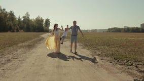 Jeune famille heureuse courant en bas de la route de campagne tenant des mains et appréciant le jour ensoleillé clips vidéos