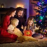 Jeune famille heureuse de quatre cadeaux de déroulement de Noël par une cheminée Photos libres de droits