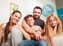 Jeune famille heureuse des parents avec la fille et le fils à la maison Image stock