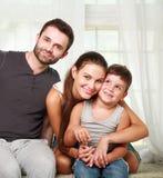 Jeune famille heureuse des parents avec le fils à la maison Photos stock