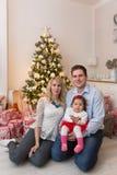 Jeune famille heureuse devant un arbre de Noël image stock