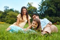 Jeune famille heureuse en stationnement Parents et enfants ayant l'amusement, jouant Image libre de droits
