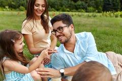 Jeune famille heureuse en stationnement Parents et enfants ayant l'amusement, jouant Photographie stock libre de droits