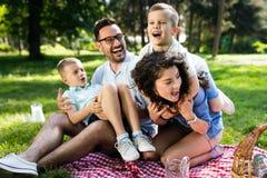 Jeune famille heureuse jouant sur l'herbe en parc et appréciant le pique-nique photographie stock libre de droits