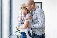 Jeune famille heureuse Le père embrasse leur bébé tout en se tenant près de la fenêtre à la maison photo stock