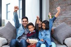 Jeune famille heureuse mangeant du maïs éclaté tout en regardant la TV Images stock