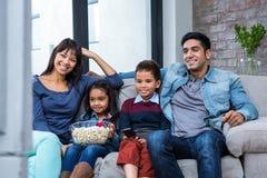 Jeune famille heureuse mangeant du maïs éclaté tout en regardant la TV Photo libre de droits