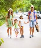 Jeune famille heureuse marchant avec la guitare passant le temps insouciant à Image stock