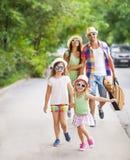 Jeune famille heureuse marchant avec la guitare passant le temps insouciant à Photos libres de droits