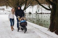 Jeune famille heureuse marchant en parc en hiver Image stock