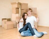 Jeune famille heureuse montrant des pouces sur un fond de carton Image stock