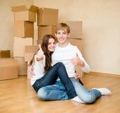 Jeune famille heureuse montrant des pouces sur un fond de carton Images stock