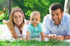 Jeune famille heureuse passant le temps extérieur sur un daycouple d'été Photos stock