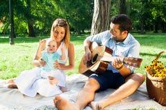 Jeune famille heureuse passant le temps extérieur sur un daycouple d'été Images libres de droits