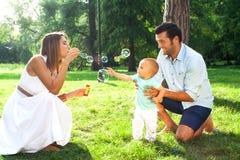 Jeune famille heureuse passant le temps extérieur sur un daycouple d'été Photos libres de droits