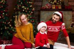 Jeune famille heureuse pendant des vacances de Joyeux Noël et de bonne année photographie stock libre de droits