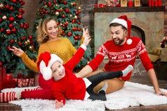 Jeune famille heureuse pendant des vacances de Joyeux Noël et de bonne année images libres de droits