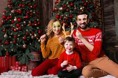 Jeune famille heureuse pendant des vacances de Joyeux Noël et de bonne année photographie stock