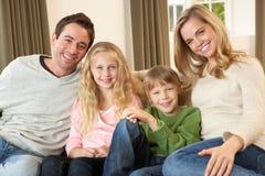 Jeune famille heureuse s'asseyant sur le sofa Photo stock