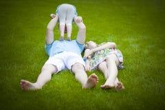 Jeune famille heureuse se trouvant sur l'herbe verte à l'extérieur Image libre de droits
