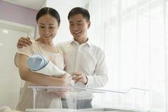 Jeune famille heureuse tenant leur nouveau-né dans la crèche d'hôpital Photo libre de droits