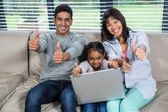 Jeune famille heureuse utilisant l'ordinateur portable avec des pouces  Photographie stock libre de droits