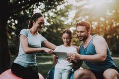Jeune famille heureuse utilisant la Tablette en parc d'été image libre de droits