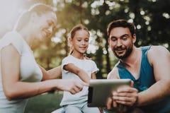 Jeune famille heureuse utilisant la Tablette en parc d'été photographie stock libre de droits