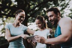 Jeune famille heureuse utilisant la Tablette en parc d'été image stock