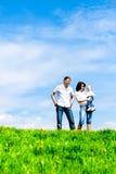 Jeune famille heureux sur l'herbe verte au-dessus du ciel photo stock