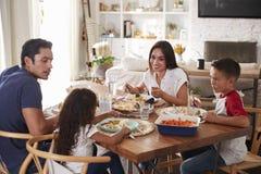 Jeune famille hispanique s'asseyant à la table de salle à manger mangeant le dîner ensemble photographie stock libre de droits