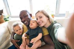 Jeune famille interraciale avec de petits enfants prenant le selfie Images stock