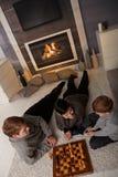 Jeune famille jouant aux échecs Image stock
