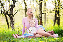 Jeune famille, mère et enfant s'asseyant dans une herbe dans le verger dessus Photographie stock