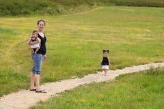 Jeune famille marchant à l'extérieur sur le journal Photographie stock