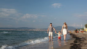 Jeune famille marchant sur la plage banque de vidéos