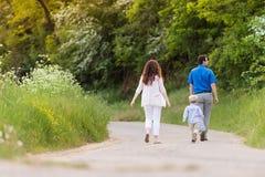 Jeune famille marchant sur la route de campagne en nature verte Images stock