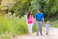 Jeune famille marchant sur la route de campagne en nature verte Photos libres de droits