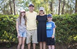 Jeune famille mignonne tous les chapeaux ou chapeaux de base-ball de port Photographie stock libre de droits