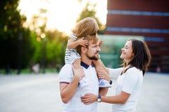 Jeune famille mignonne un jour d'été dans la place de ville Image libre de droits