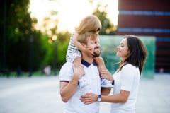 Jeune famille mignonne un jour d'été dans la place de ville Photos libres de droits