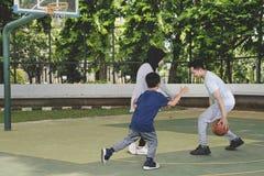 Jeune famille musulmane jouant au basket-ball dans le domaine image stock