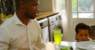 Jeune famille noire ayant la nourriture à la table de salle à manger dans la cuisine de la maison confortable 4k clips vidéos